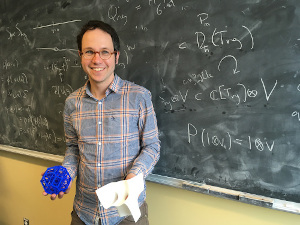 Joel Kamnitzer holding math objects in front of a black board